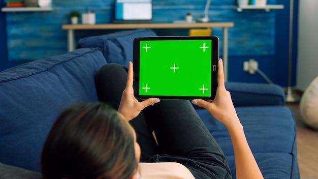 Vista da sopra la spalla di una donna casual seduta sul divano che utilizza un computer tablet con chroma key schermo verde