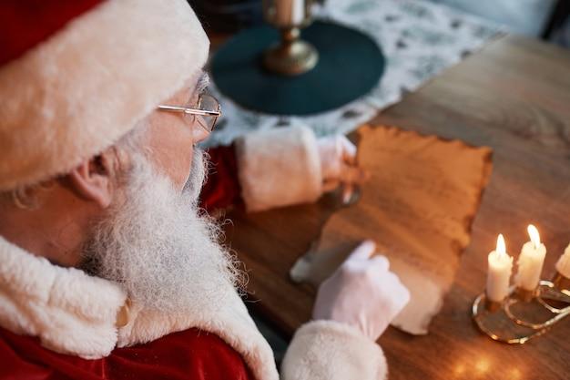 Vista da sopra la spalla di babbo natale con gli occhiali seduto a tavola e leggendo la lettera sotto il lume di candela