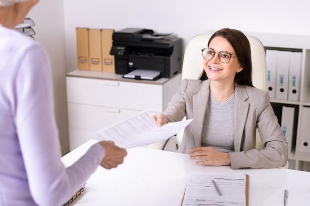 Sopra la vista della spalla della signora maggiore che dà il modulo riempito all'assistente sociale amichevole sorridente in ufficio