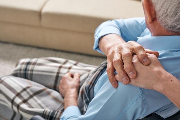 Sopra la vista della spalla dell'uomo anziano con la coperta sulle gambe che tocca la mano del parente sulla sua spalla e sensazione di sostegno