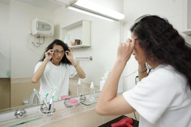 Vista da sopra la spalla di un giovane ragazzo vietnamita serio con i capelli lunghi in piedi davanti allo specchio in bagno e che regola gli occhiali