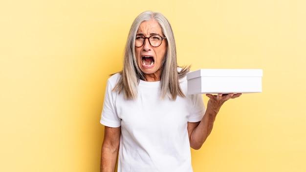 Gridare in modo aggressivo, sembrare molto arrabbiato, frustrato, indignato o infastidito, urlare di no e tenere in mano una scatola bianca