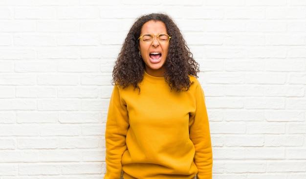Gridando in modo aggressivo, sembrando molto arrabbiato, frustrato, oltraggiato o infastidito, urlando di no