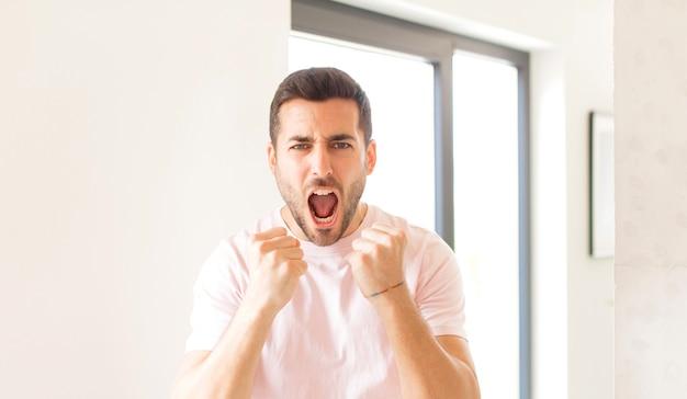 Gridando in modo aggressivo con sguardo infastidito, frustrato, arrabbiato e pugni stretti, sentendosi furioso