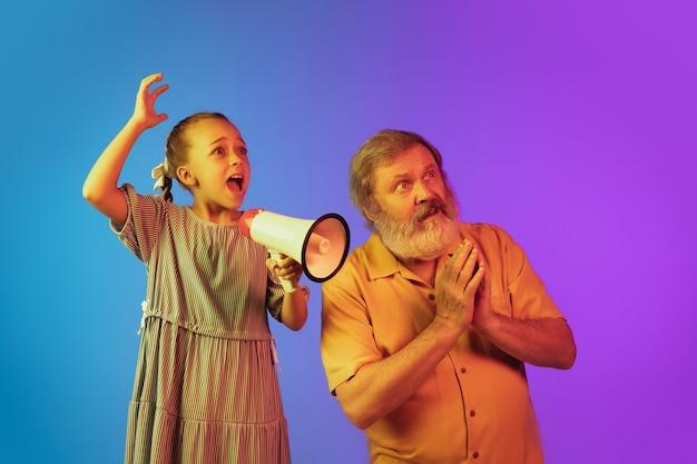 Gridando con il megafono. uomo anziano che trascorre del tempo felice con la nipote al neon. stile di vita anziano gioioso, famiglia, infanzia, concetto tecnologico, vendite. godendo gridando con il megafono. copyspace.