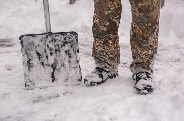La pala per sgombrare la neve si trova accanto ai piedi di un uomo con gli stivali invernali