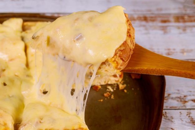 Pala tenendo la fetta di pizza al formaggio