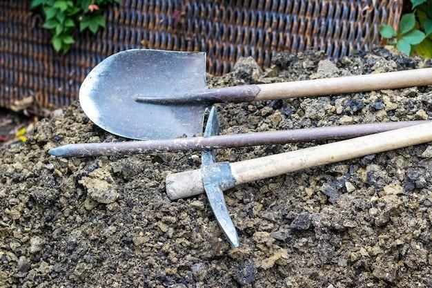 Pala, piccone e rottami su un mucchio di terra. strumenti per scavare trincee