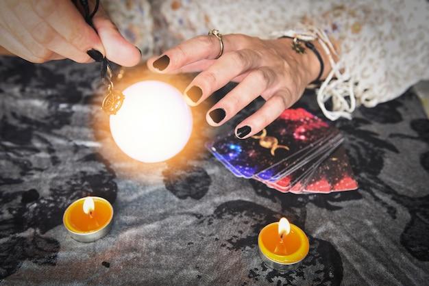 Mostra indovini delle mani che tengono le carte dei tarocchi e il lettore di tarocchi con lume di candela e sfera di cristallo magica, eseguendo letture spettacoli magici, concetto di previsione di astrologi mistici di cose