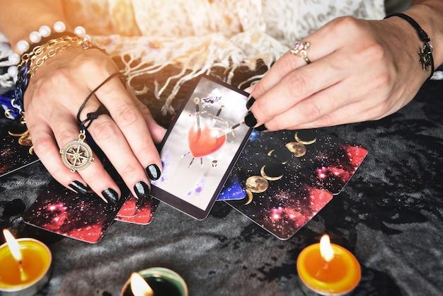 Mostra indovini delle mani che tengono le carte dei tarocchi e il lettore di tarocchi con la luce della candela sul tavolo, eseguendo letture spettacoli magici, cose mistiche astrologi concetto di previsione