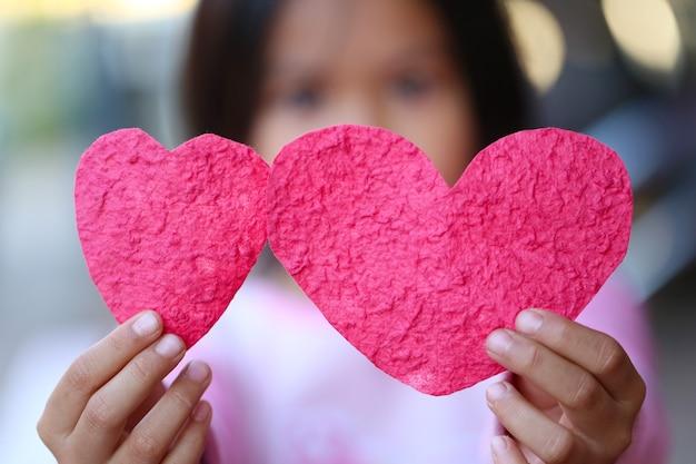 Mostra la forma del cuore vuoto rosso sulla mano del bambino per il concetto di amore e pace.