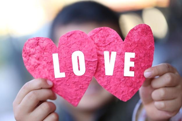 Mostra la forma del cuore rosso e il testo d'amore sulla mano del bambino per il concetto di amore e il giorno di san valentino.