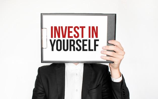 Mostra parola di attesa su carta mostrata da uomo d'affari isolato. testo investire in te stesso