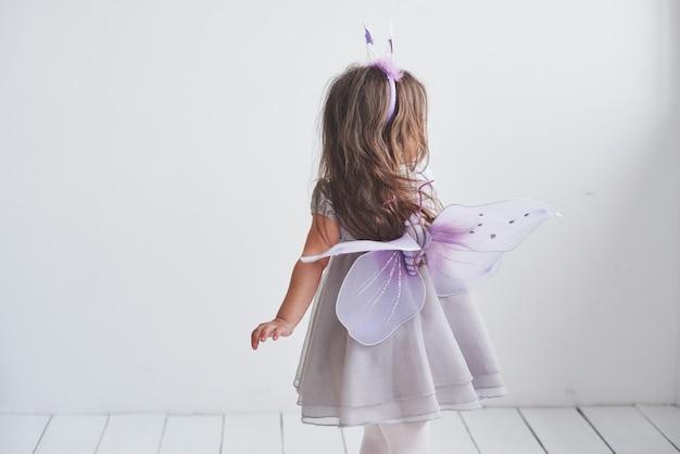 Mostra le tue ali. bella bambina con il costume da fata in piedi nella stanza.