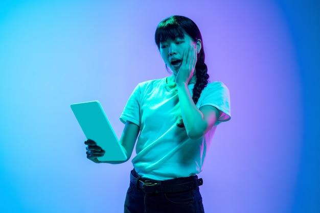 Mostrando lo schermo del telefono vuoto ritratto di giovane donna asiatica su gradiente bluepurple studio
