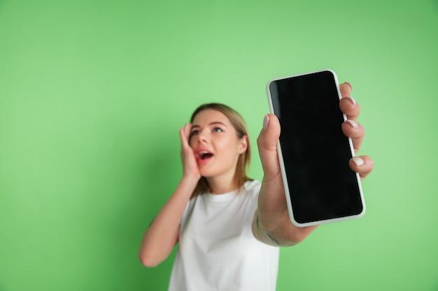 Visualizzazione dello schermo vuoto. il ritratto della giovane donna caucasica isolato sulla parete verde. bellissimo modello femminile in camicia bianca. concetto di emozioni umane, espressione facciale, giovinezza.