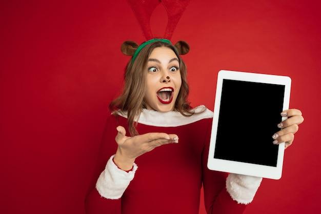 Mostra schermo tablet vuoto, . bella donna caucasica con i capelli lunghi come la confezione regalo di cattura delle renne di babbo natale.