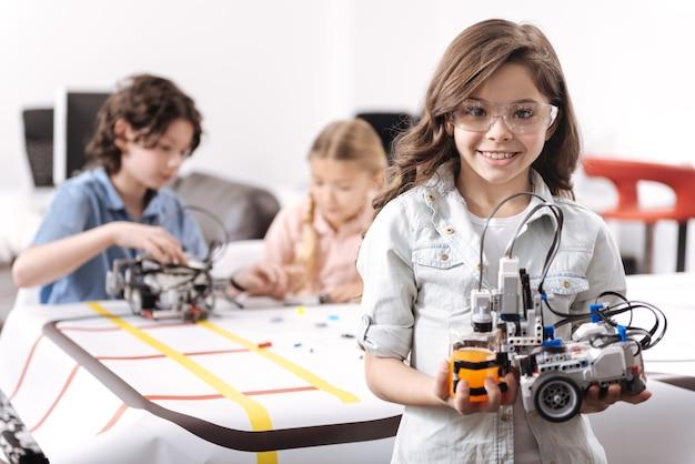 Mostrando il mio talento. sorridente ragazza allegra felice in piedi a scuola e tenendo il robot mentre i colleghi lavorano al progetto