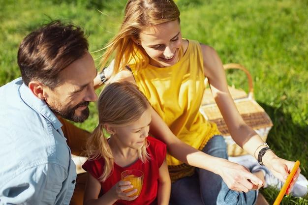 Mostrando le foto. madre bionda allegra che tiene una compressa mentre fa un picnic con la sua famiglia