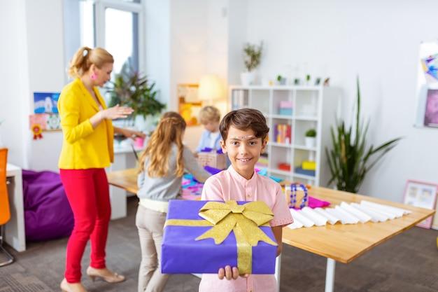 Mostrando la casella presente. bel ragazzo dai capelli scuri che mostra una bella scatola regalo dopo averla decorata in classe