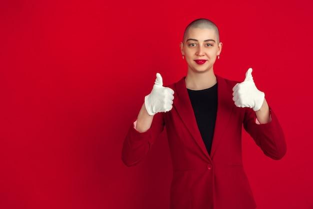 Mostrando i pollici in su. ritratto di giovane donna calva caucasica isolata sulla parete rossa. bellissimo modello femminile in giacca. emozioni umane, espressione facciale, vendite, concetto di annuncio. cultura pazzesca.