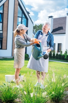 Mostrando la via. moglie amorevole premurosa che indossa guanti arancioni che mostra al marito il modo di annaffiare le piante