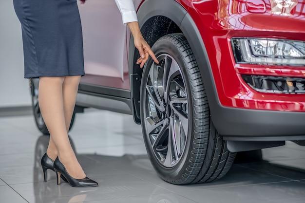 Showroom. rappresentante femminile della concessionaria in piedi vicino all'auto nello showroom