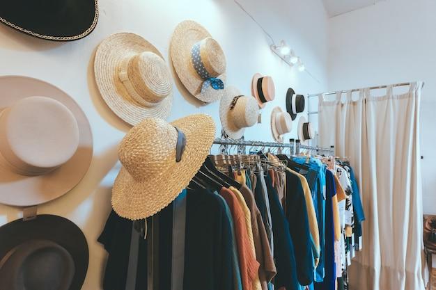 Negozio showroom di abbigliamento femminile e cappelli di paglia estivi appesi al muro. appendiabiti con abiti colorati. interni moderni e minimalisti
