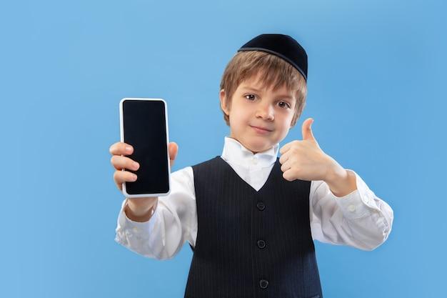 Mostra lo schermo del telefono vuoto. ritratto del ragazzo ebreo ortodosso isolato sulla parete blu dello studio.
