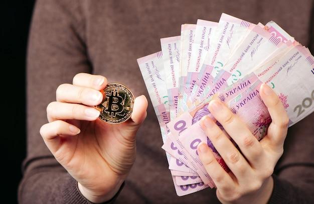 Mostra una moneta d'oro bitcoin - un simbolo di criptovaluta, nuovi soldi virtuali e una pila di soldi in grivna ucraina, messa a fuoco selettiva, tonica.