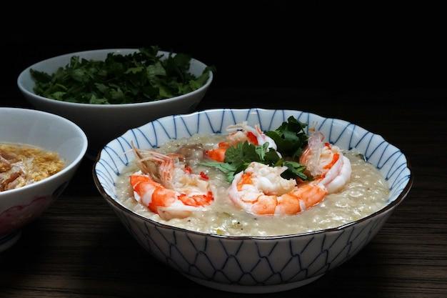 Zuppa di riso bollito o porridge di gamberi in una ciotola con aglio fritto e olio di coriandolo