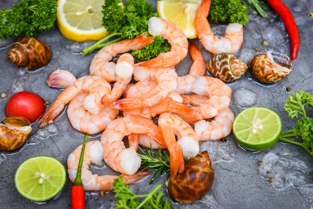 Gamberetti pelati su fondo scuro per cucinare, gamberi freschi o gamberi frutti di mare e crostacei