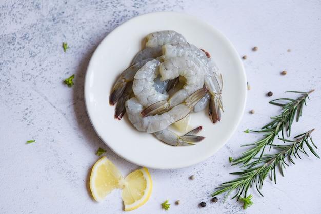 Gamberetti pelati su piastra bianca pronti per la cottura con erbe e spezie limone, gamberi freschi o gamberi