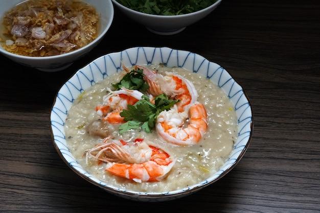 Porridge di gamberi in una ciotola con aglio fritto e olio di coriandolo su un tavolo di legno