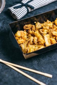 Gamberi, calamari e polpi cotti in pastella in una scatola di carta nera su fondo scuro.