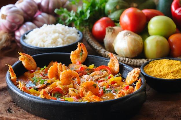 Stufato di gamberi in una ciotola di argilla con riso e farina di manioca. cucina brasiliana.