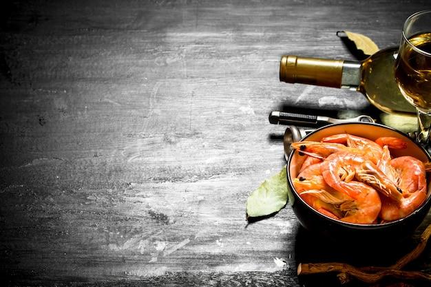Gamberetti con vino bianco e un cavatappi sulla lavagna nera