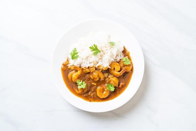 Gamberetti in salsa al curry su riso ricoperto