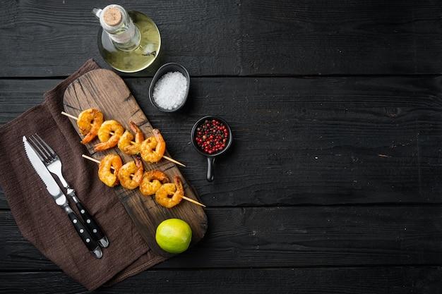 Gamberetti su spiedini con salsa al curry di chutney di mango, sul tavolo di legno nero
