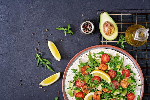 Tacos di tortilla di gamberi a faccia aperta avvolgere con verdure fresche. cibo salutare. pasto messicano. vista dall'alto. disteso