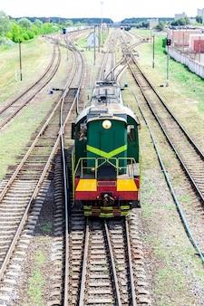 Una locomotiva da manovra si muove lungo la ferrovia dalla stazione per smistare i vagoni ferroviari. trattore ferroviario per unire i vagoni in un treno.