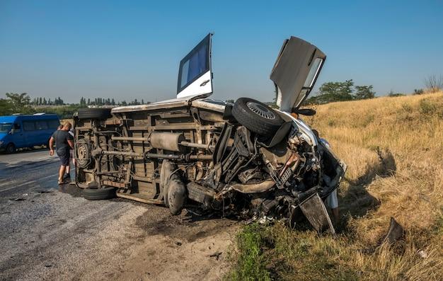 Shuttle bus capovolto dopo la collisione con l'auto. le persone hanno sofferto nell'incidente. situazione pericolosa sulla strada.
