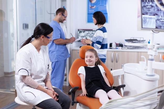 Bambina timida che guarda il medico dentista in attesa del trattamento della cavità dei denti. bambino con sua madre durante il controllo dei denti con stomatolog seduto su una sedia.