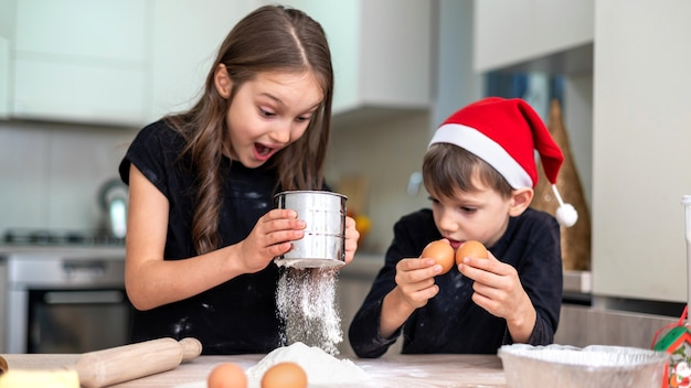 I fratelli stanno cucinando in cucina, ragazzo con cappello di natale. idea per bambini felici