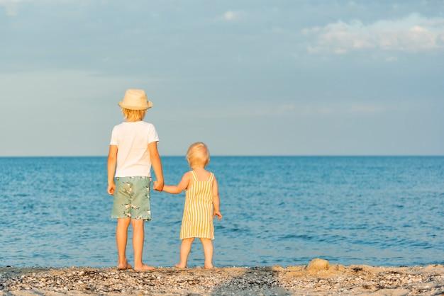Fratelli in spiaggia. vista posteriore. il fratello tiene la mano della sorellina.