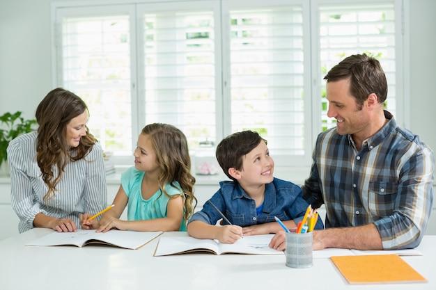 Fratelli che ricevono aiuto con i compiti dai genitori
