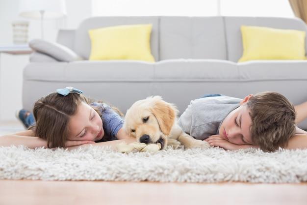Fratelli germani che dormono con il cane sul tappeto