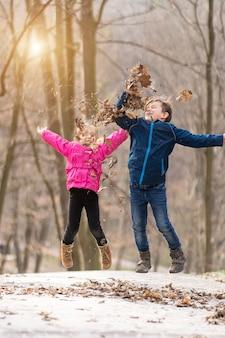 Fratelli germani insieme che saltano in una foresta con foglie secche in inverno