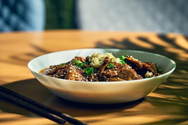 Manzo piccante del sichuan in salsa piccante, aglio, pepe, semi di sesamo in una ciotola bianca. cucina cinese. shuizhu, shui zhu
