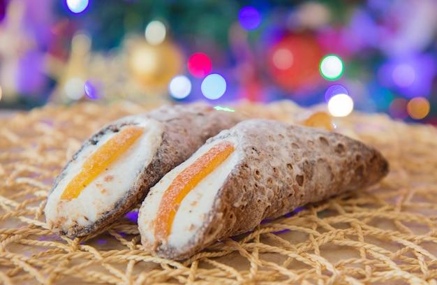 Cannolo siciliano con canditi all'arancia con luci natalizie come sfondo